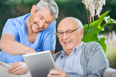 Caregiver and an elder man watching something funny in the tablet